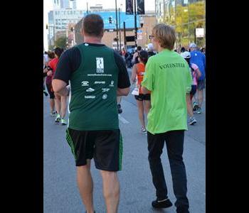 Andrew running side by side a Marathon Runner