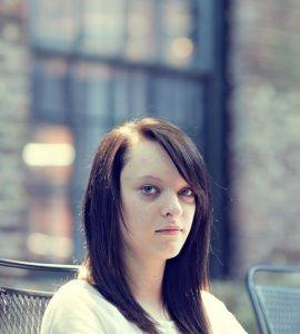 A sullen teenage girl looks unsmiling at the camera.