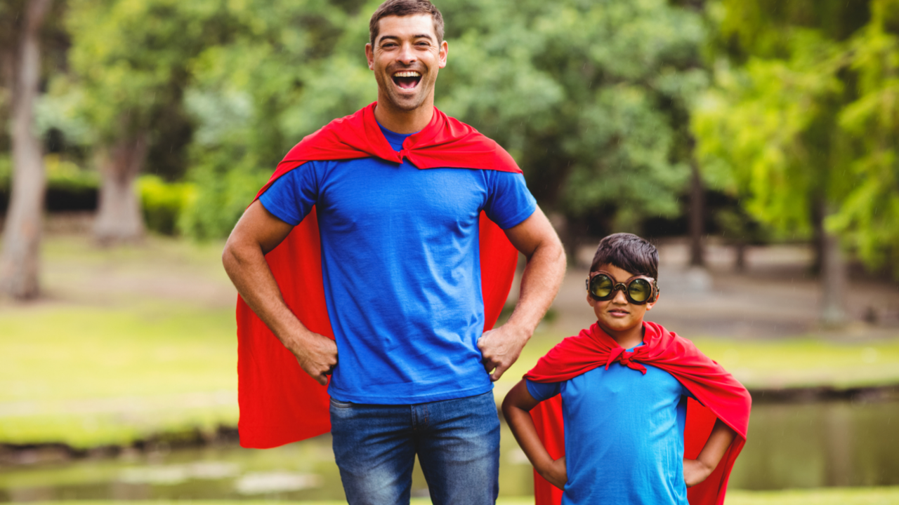 Father and son smiling and wearing superhero capes