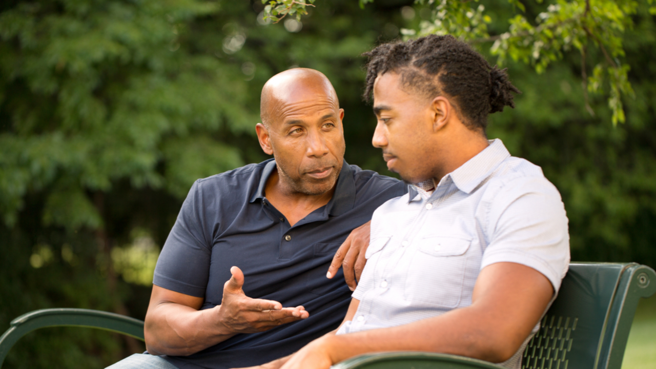 Male mentor and male mentee sitting outside in a park