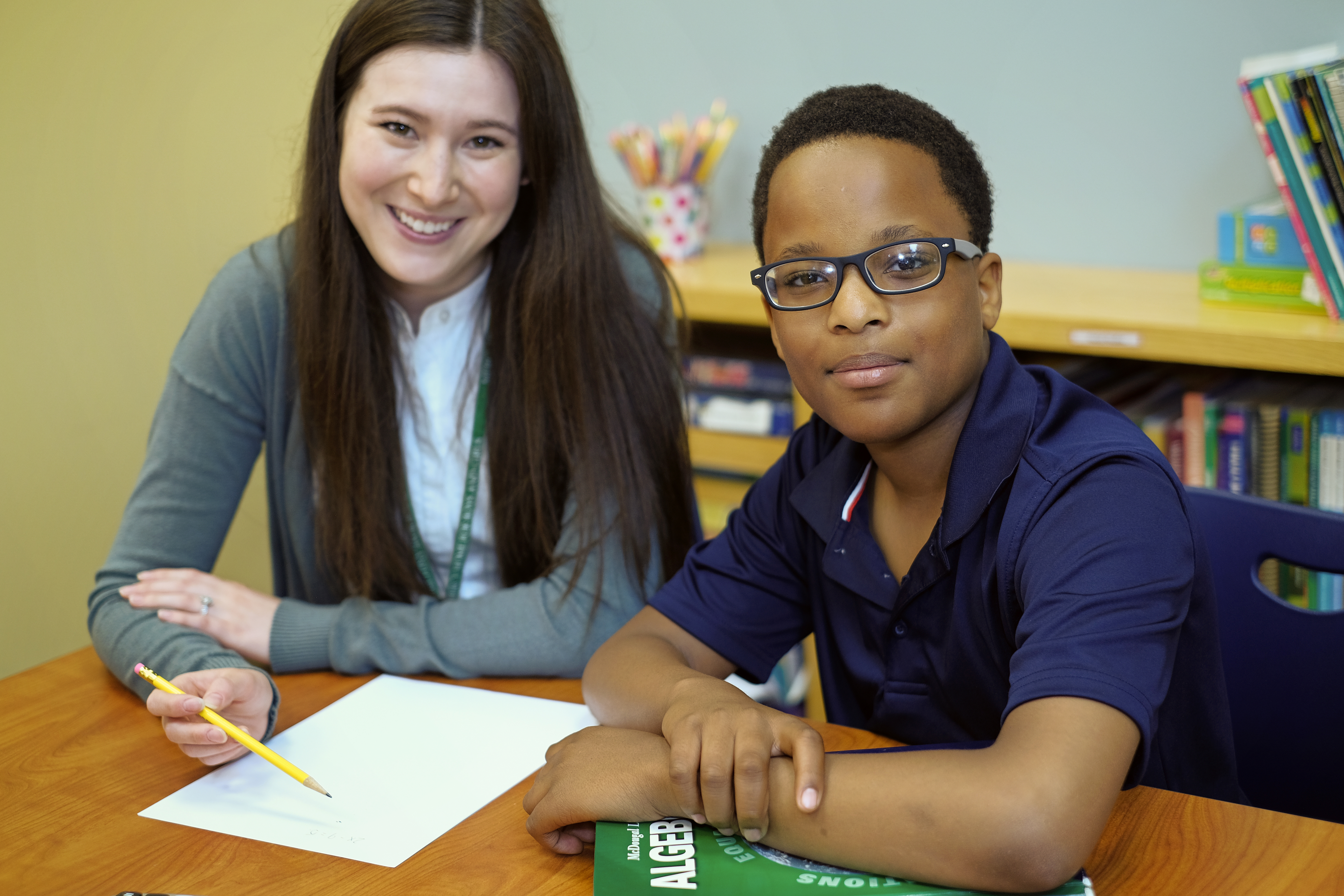 Young boy sitting at table with female tutor