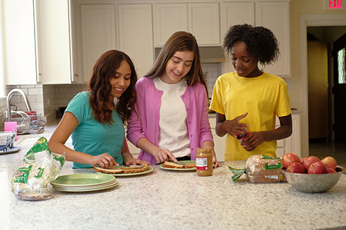 young girls making a sandwich in a kitchen