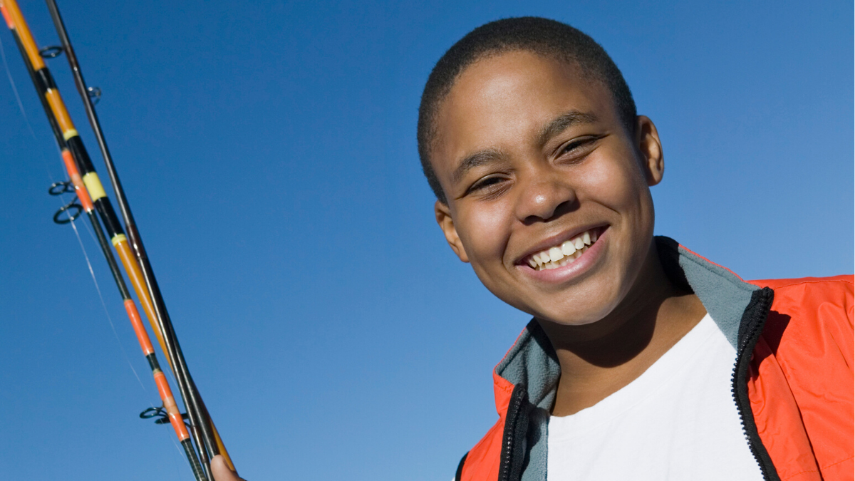 Young smiling boy with fishing rod