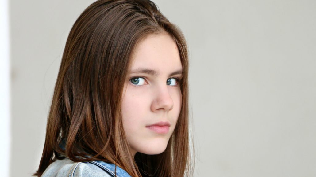 Young girl looking at the camera with a frown