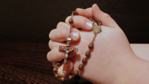 Hands folded in prayer with rosary