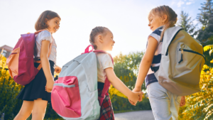 Young girls with backpacks on holding hands and smiling