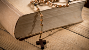 Bible with rosary draped across it